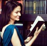 Ritratto del libro di lettura della giovane donna di bellezza nel sorridere delle biblioteche, Immagini Stock Libere da Diritti