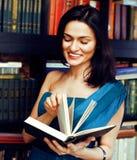 Ritratto del libro di lettura della giovane donna di bellezza nel sorridere delle biblioteche, Immagine Stock