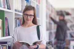 Ritratto del libro di lettura dello studente del famale in biblioteca Fotografie Stock