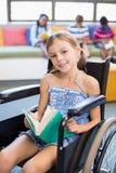 Ritratto del libro di lettura disabile della ragazza della scuola in biblioteca Immagini Stock