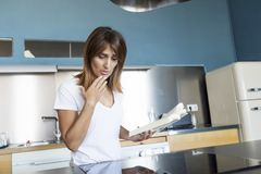 Ritratto del libro di lettura sorridente della giovane donna in cucina a casa immagini stock libere da diritti