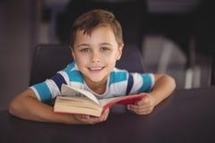 Ritratto del libro di lettura sorridente della scolara in biblioteca Immagine Stock