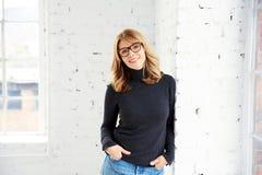 Ritratto del maglione e dei jeans di collo di cilindro d'uso della donna attraente mentre esaminando macchina fotografica e sorri fotografia stock