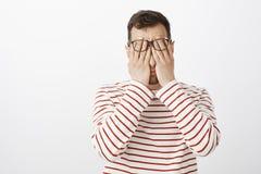 Ritratto del maschio adulto stanco laborioso in pullover e vetri a strisce, fronte di lucidatura con le palme, ritenenti stanche  Fotografie Stock