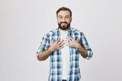 Ritratto del maschio barbuto adulto piacevole con il sorriso felice sincero, tenentesi per mano sul petto che esprime sorpresa me Fotografia Stock