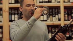 Ritratto del maschio bello che vetro di vino odorante Un tipo con una bottiglia di vino e di un vetro di vino in sue mani che sta archivi video