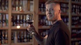 Ritratto del maschio bello nel profilo che tiene il vetro di vino L'uomo ammira la bevanda alcolica stock footage