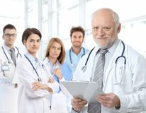 Ritratto del medico invecchiato con i residenti medici Immagini Stock Libere da Diritti