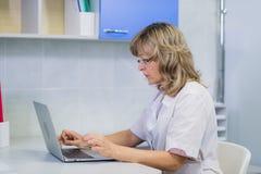 Ritratto del medico specialista sul lavoro, esaminando computer portatile, funzionante immagini stock