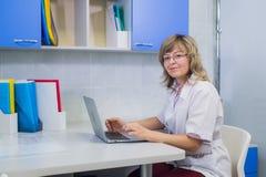 Ritratto del medico specialista sul lavoro, esaminando macchina fotografica, sorridente immagini stock libere da diritti