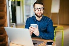 Ritratto del messaggio sorridente della lettura dell'uomo di affari con lo smartphone in ufficio Fotografia Stock