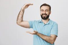 Ritratto del modello maschio bello con la barba ed il taglio di capelli d'avanguardia che si tengono per mano come la mostra dell Immagini Stock