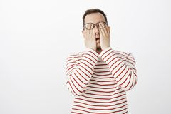Ritratto del modello maschio scomodo esaurito in pullover e vetri a strisce, occhi di lucidatura, dolore ritenente o essere Immagini Stock
