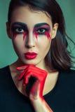 Ritratto del mostro strano con trucco colorato sporco di disordine sul suo fronte gridare donna con gli strappi e la mano sanguin Fotografie Stock