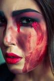 Ritratto del mostro strano con trucco colorato sporco di disordine sul suo fronte gridare donna con gli strappi e la mano sanguin Immagine Stock Libera da Diritti