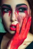 Ritratto del mostro strano con trucco colorato sporco di disordine sul suo fronte gridare donna con gli strappi e la mano sanguin Immagini Stock Libere da Diritti