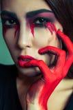 Ritratto del mostro strano con trucco colorato sporco di disordine sul suo fronte gridare donna con gli strappi e la mano sanguin Fotografia Stock Libera da Diritti