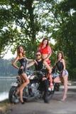 Ritratto del motociclista e di tre ragazze sexy Fotografia Stock