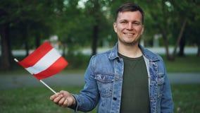Ritratto del movimento lento del cittadino austriaco fiero che ondeggia bandiera ufficiale dell'Austria, sorridente ed esaminante video d archivio