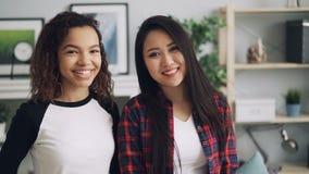 Ritratto del movimento lento degli amici razza mista asiatico e afroamericano degli studenti graziosi che esaminano macchina foto archivi video