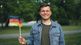 Ritratto del movimento lento della bandiera ufficiale d'ondeggiamento turistica tedesca allegra della Germania, sorridendo ed esa stock footage