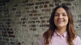 Ritratto del movimento lento della giovane donna attraente in abbigliamento casual che esamina macchina fotografica che sorride e archivi video