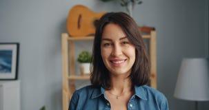 Ritratto del movimento lento della giovane donna incantante che esamina macchina fotografica che sorride a casa video d archivio