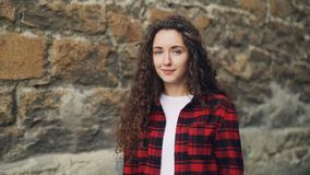 Ritratto del movimento lento della giovane donna sorridente con la maglietta bianca d'uso lunga dei capelli ricci e la condizione archivi video