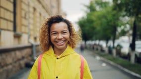 Ritratto del movimento lento della ragazza afroamericana felice che sorride e che esamina macchina fotografica che sta all'aperto video d archivio
