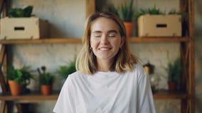 Ritratto del movimento lento della ragazza allegra con capelli biondi che osservano stare sorridere e di risata della macchina fo video d archivio