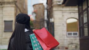 Ritratto del movimento lento della ragazza asiatica attraente che cammina nella via con i sacchetti della spesa, tornitura, sorri stock footage