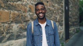 Ritratto del movimento lento dello studente afroamericano bello del tipo che sorride e che esamina macchina fotografica che sta a video d archivio