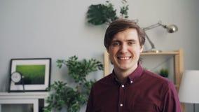 Ritratto del movimento lento dello studente bello che esamina macchina fotografica con il sorriso a casa archivi video