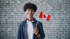 Ritratto del movimento lento dello studente sveglio che tiene bandiera canadese sul fondo del mattone stock footage