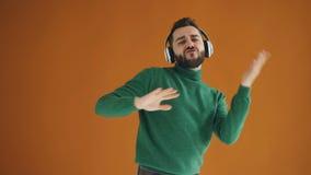 Ritratto del movimento lento di ascoltare ballante del tipo allegro la musica in cuffie stock footage