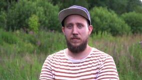 Ritratto del movimento lento di giovane uomo divertente barbuto con lo sguardo del cappuccio in camera video d archivio