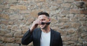 Ritratto del movimento lento di sorridere barbuto alla moda degli occhiali da sole di decollo del tipo video d archivio
