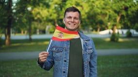 Ritratto del movimento lento del giovane bello con il fronte espressivo che ondeggia bandiera ufficiale spagnola, sorridente ed e video d archivio