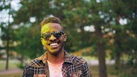 Ritratto del movimento lento del tipo afroamericano barbuto in occhiali da sole, fronte e capelli coperti di pittura della polver archivi video