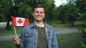 Ritratto del movimento lento del tipo bello in abbigliamento casual che ondeggia bandiera canadese, sorridente ed esaminante macc stock footage