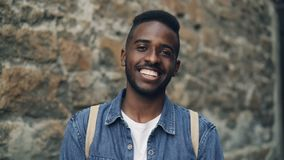 Ritratto del movimento lento del turista afroamericano sorridente dell'uomo con lo zaino che esamina macchina fotografica che sta stock footage