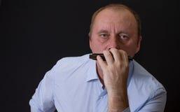 Ritratto del musicista maturo che porta camicia a strisce blu che gioca armonica a bocca fotografia stock