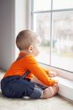 Ritratto del neonato caucasico adorabile sveglio che si siede sul windowsi Fotografia Stock