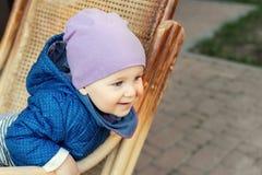 Ritratto del neonato caucasico adorabile sveglio divertendosi seduta nella sedia di oscillazione di legno del rattan sul cortile  fotografie stock