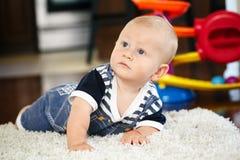 Ritratto del neonato sorridente caucasico biondo adorabile sveglio con gli occhi azzurri che si trovano sul pavimento nella stanz Fotografie Stock Libere da Diritti