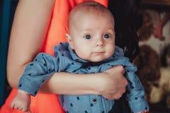Ritratto del neonato sulle mani delle madri Camicia, arco del legame e pantaloni blu d'uso Foto alta vicina di stile di vita Immagini Stock