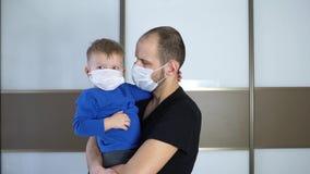 Ritratto del padre che tiene il piccolo bambino sveglio del neonato del bambino che indossano maschera medica protettiva, papà e  archivi video