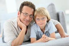 Ritratto del padre e del figlio che si trovano sul sofà Fotografia Stock