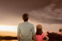 Ritratto del padre e della figlia che godono della vista di tramonto fotografia stock