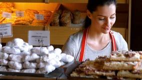 Ritratto del panettiere femminile che tiene alimento dolce in vassoio video d archivio
